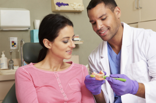 Dentist Demonstrating How To Brush Teeth To Female Patient