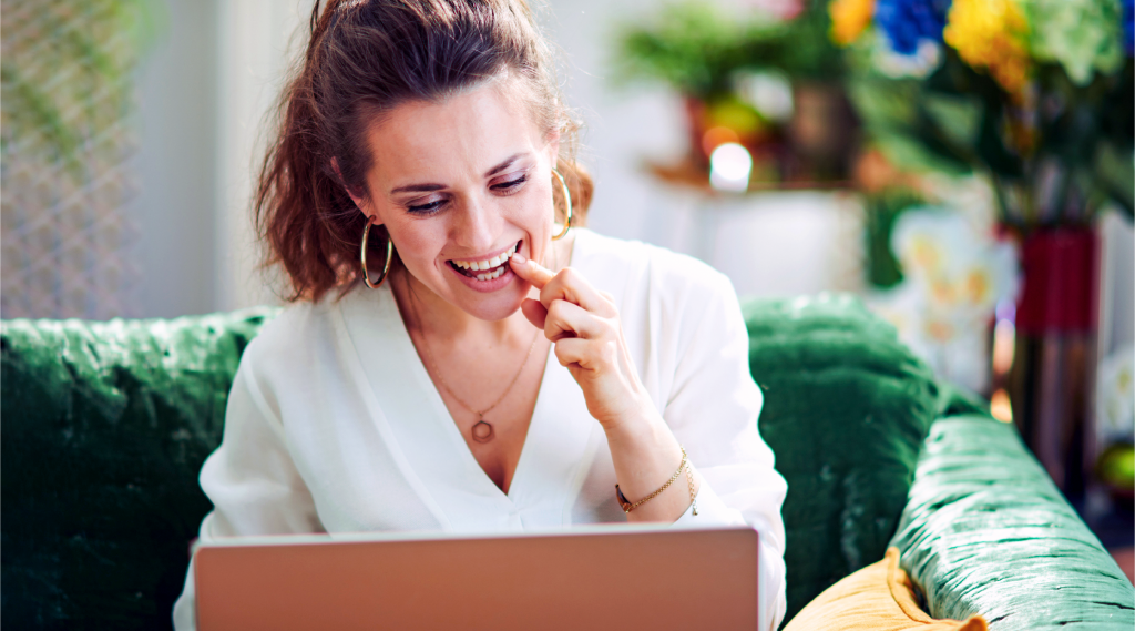 Woman smiles while looking at computer screen